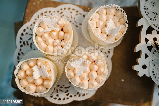 992836992 istock photo Table with cakes, sweets, candy, buffet. Dessert table for a party goodies for the wedding banquet area. Close up. candy bar. Decorated delicious. 1132126387