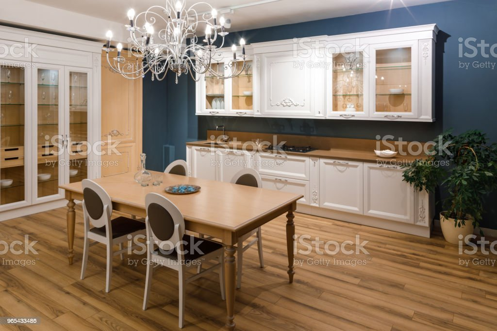Table with chairs in stylish kitchen with chandelier zbiór zdjęć royalty-free