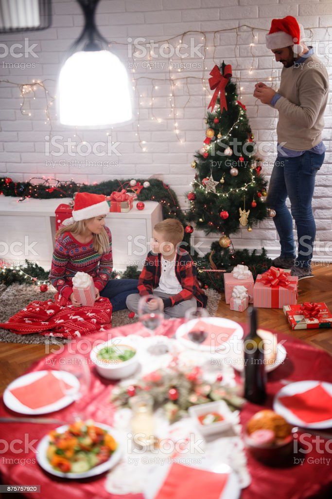 Christmas Gifts For New Parents.Table With Christmas Lunch In Front Of Young Parents