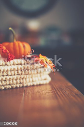 Table with cozy blanket and Thanksgiving pumpkin arrangement