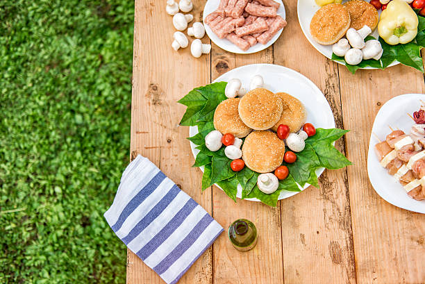 table with food and drink ready for barbecue party - picknick tisch kühler stock-fotos und bilder