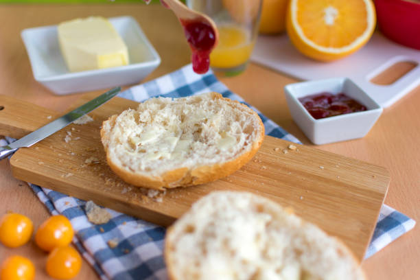 Tisch mit einer halben Rolle mit Butter auf eine Marmelade aus einem Löffel getrunken – Foto