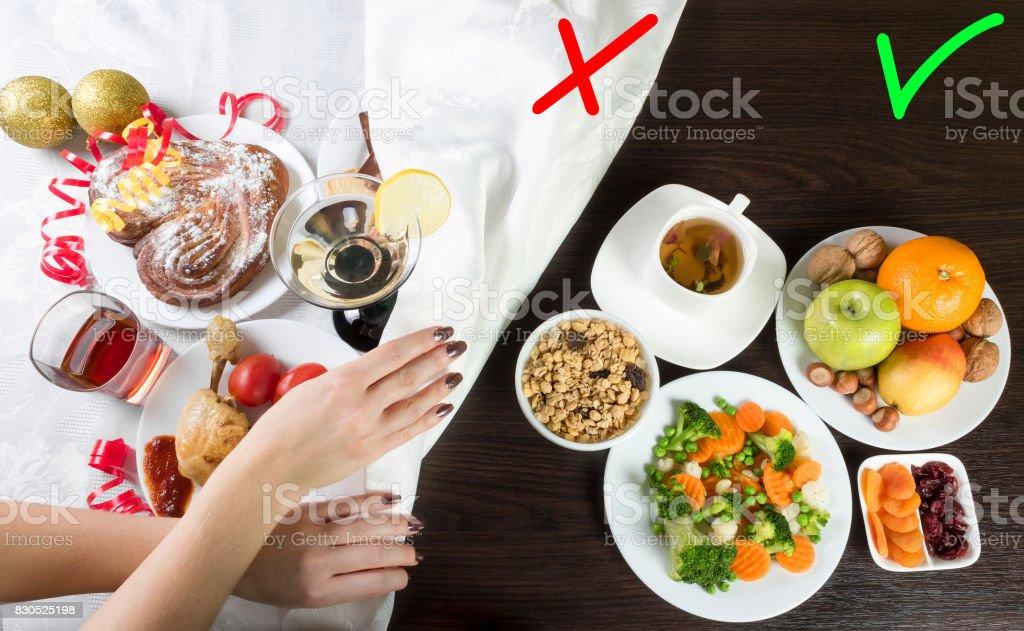 健康と不健康な食品やアルコールを持つテーブル。女性の有害な料理の一部を覆う手し、テーブル クロスと飲み物。 ストックフォト