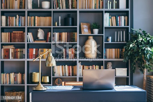 Table with laptop in home office interior
