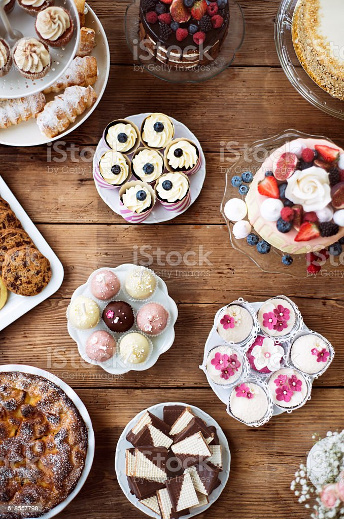 Table with loads of cakes, cupcakes, cookies and cakepops. stock photo