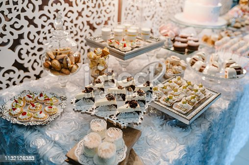992836992 istock photo Table with muffins, cakes, sweets, candy, buffet. Dessert table for a party goodies for the wedding banquet area. Close up. candy bar. Decorated delicious. 1132126383