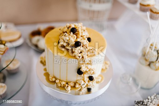 992836992istockphoto Table with muffins, cakes, sweets, candy, buffet. Dessert table for a party goodies for the wedding banquet area. Close up. candy bar. Decorated delicious. 1159580390