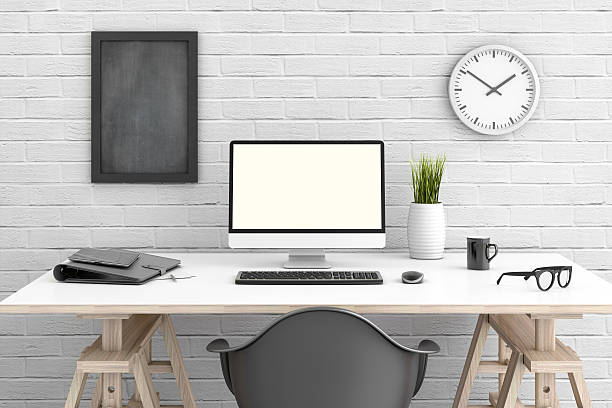 Table with pc in front of a white wall stock photo