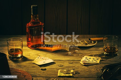 Table with playing cards, whiskey, cigar and weapons. Cowboy still life.