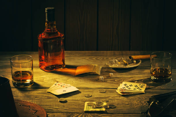 Table with playing cards, whiskey, cigar and weapons Table with playing cards, whiskey, cigar and weapons. Cowboy still life. gangster stock pictures, royalty-free photos & images