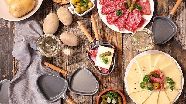 table with raclette cheese, meat and potato - raclette stock-fotos und bilder
