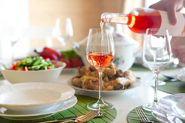 Table with rose wine, fish soup, salad and chiken stock photo