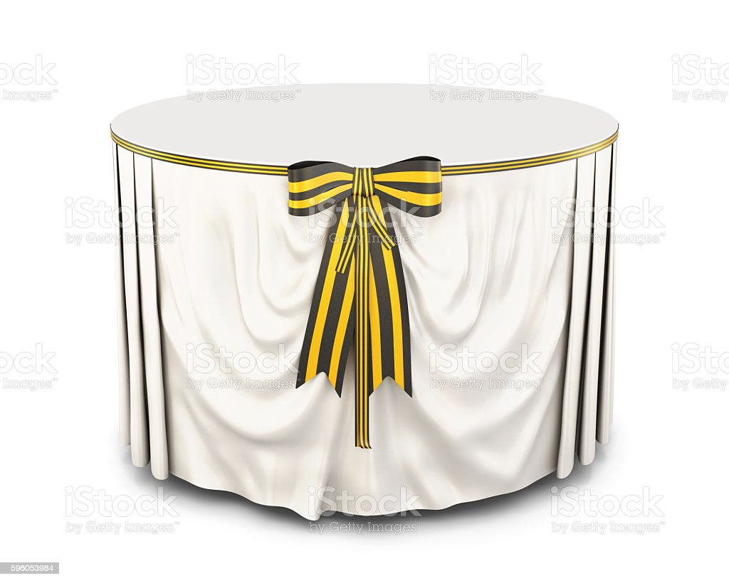 Table with tablecloth and bow on a white background. stock photo