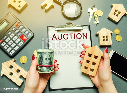 1050485096 istock photo Table with the word Auction. The women auctioneer is holding money in the hands of dollars and a wooden house. Purchase and public sale of real estate. Sell or buy a house / apartment 1097823656