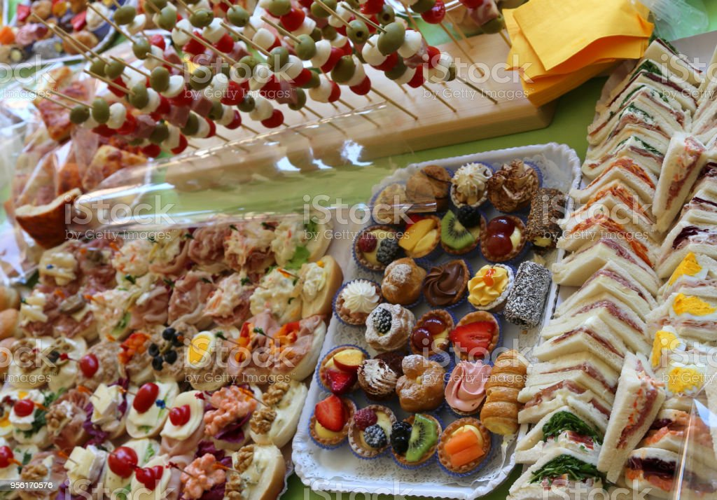 table with trays with pastries sandwiches skewers with olives mo stock photo