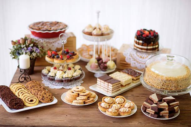 mesa con varias galletas, tartas, pasteles, cupcakes y cakepops - postre fotografías e imágenes de stock