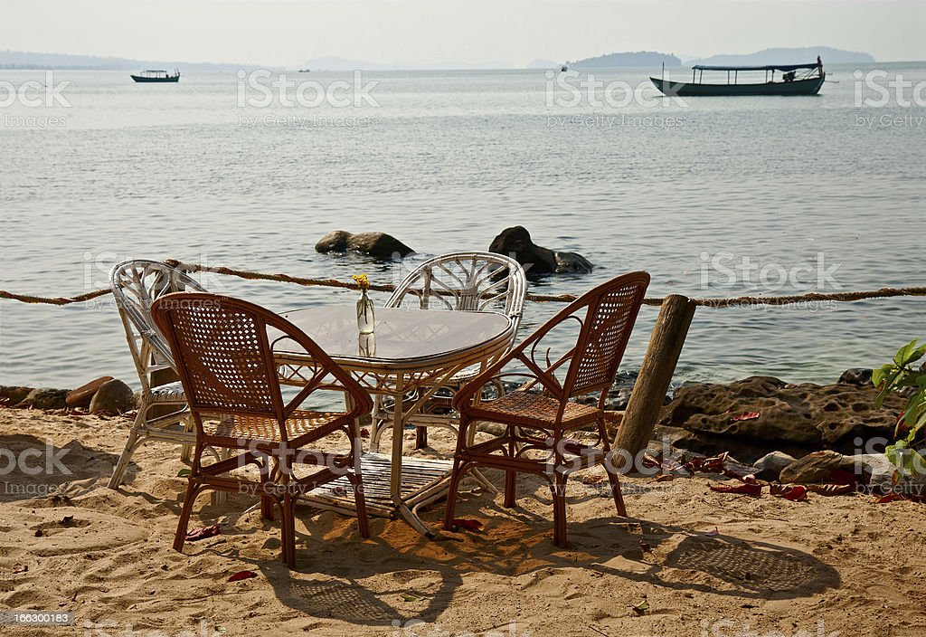 Table with wicker chairs on seacoast royalty-free stock photo