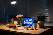 Table with laptop, flowers, food and drink, makeup items, copybook, eyeglasses, alarm clock and lamp over all that stuff in the darkness