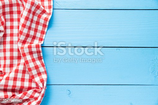 Checkered tablecloth over colorful wooden table. Top view.