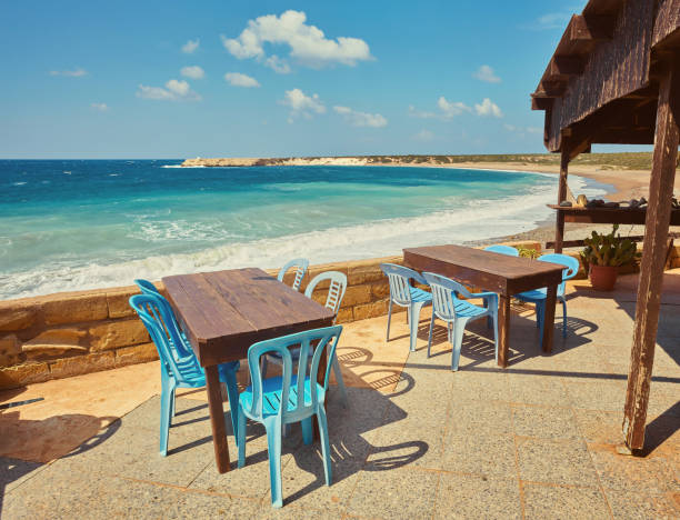 Tables and chairs in a cafe with palm trees on the beach Lara stock photo
