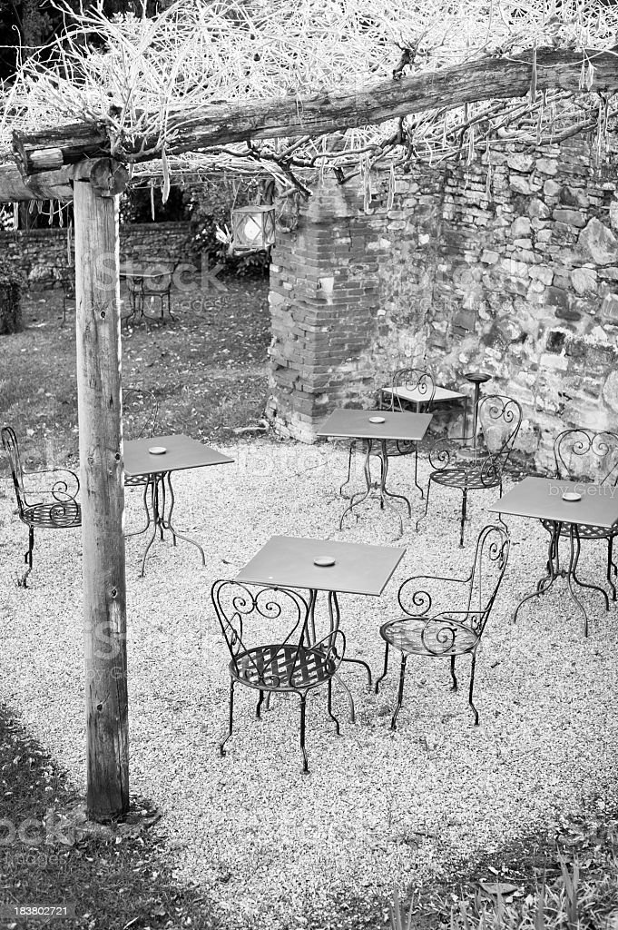 Tables And Chairs Under Rustic Wisteria Porch royalty-free stock photo