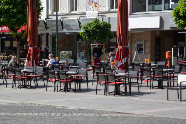 Tables and chairs with reduced number of guests in front of a pub based on pandemic restrictions