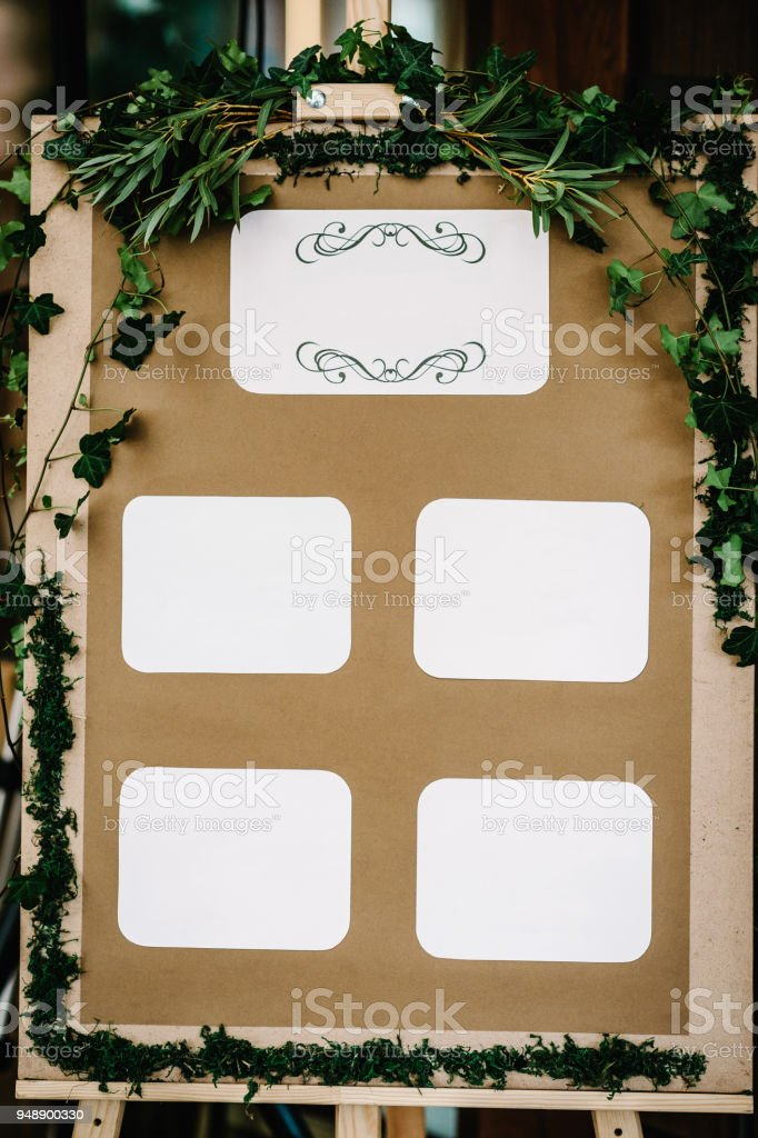 Tables wedding guests on the easel on wedding reception. The frame is decorated with green flowers and greenery. List, plan, chart of the seating area of guests at the tables at restaurant. stock photo