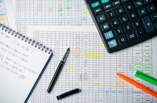 Tables with accounting calculations, paper notebook with records, calculator, pen and highlighter