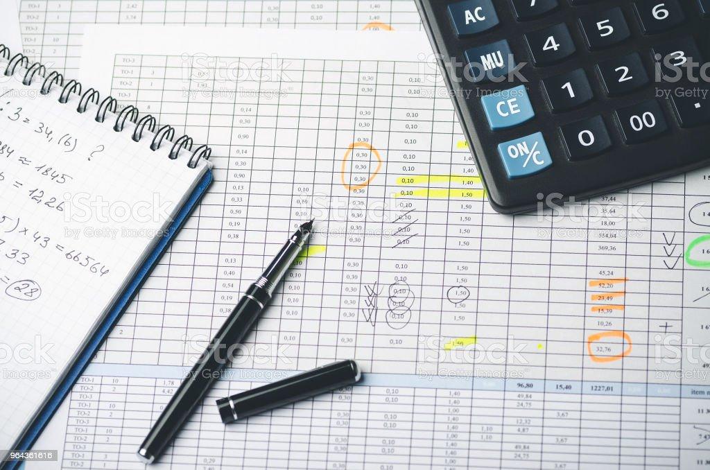 Tabelas com valores contábeis, caneta, caderno de papel e calculadora - Foto de stock de Ajustando royalty-free