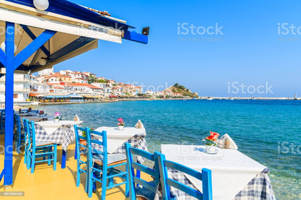 Tables with chairs in traditional Greek tavern in Kokkari town on coast of Samos island, Greece stock photo