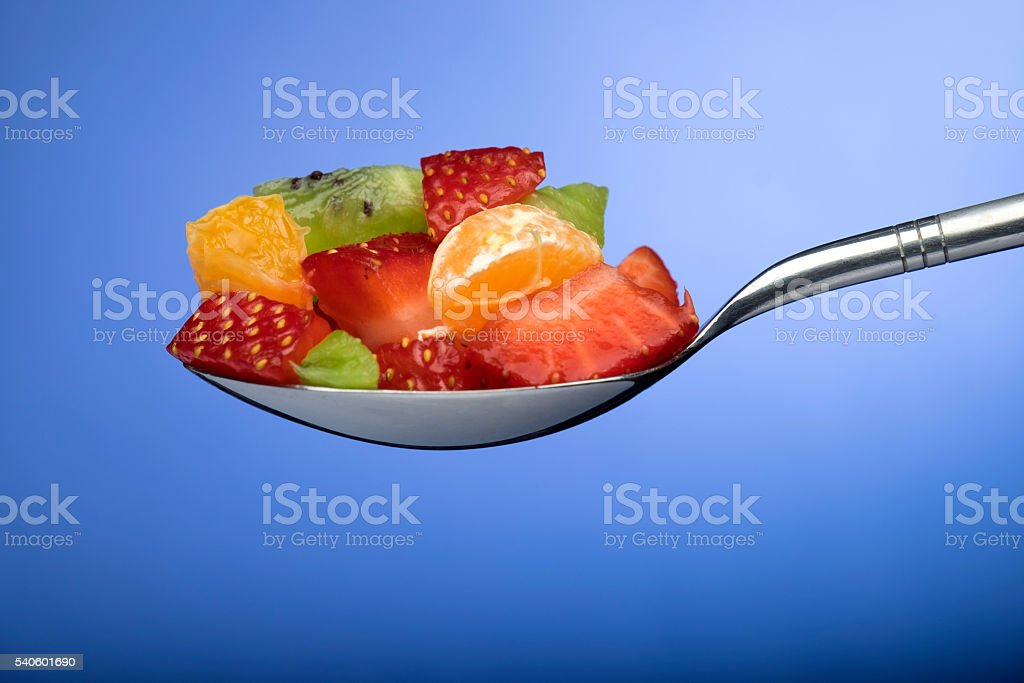 tablespoon with pieces of fruits stock photo