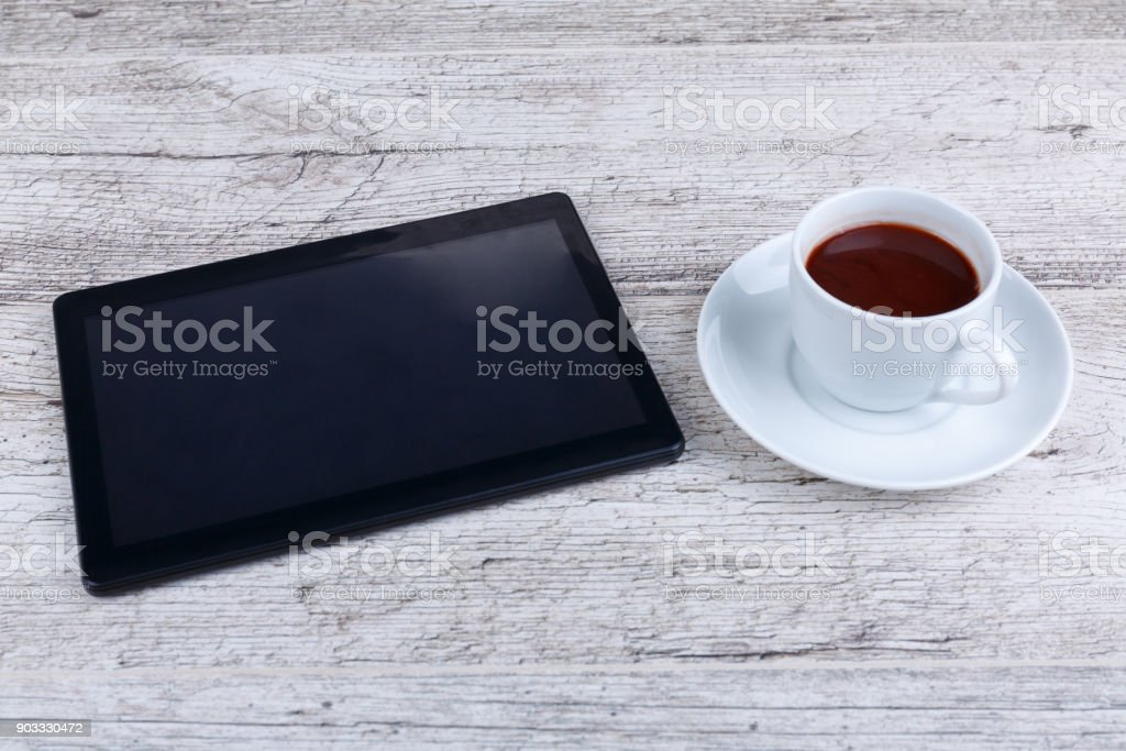 A tablet and beside a cup with a fragrant coffee on a wooden table. stock photo