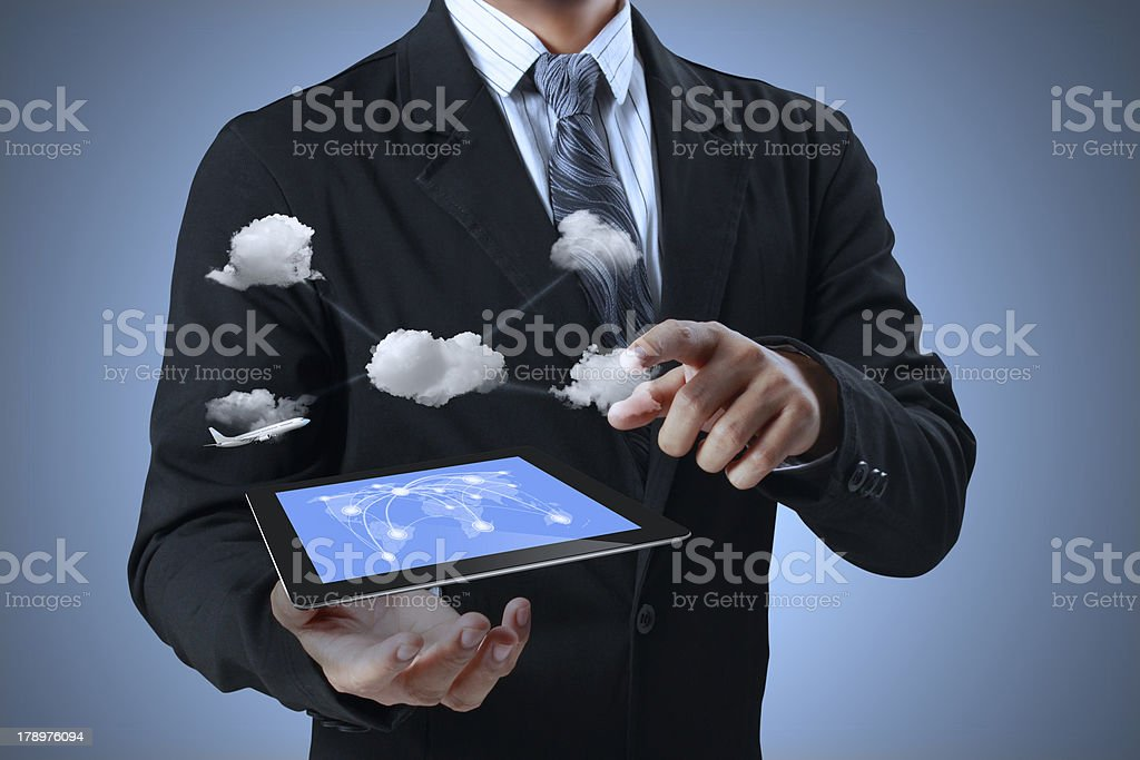 A tablet and clouds floating in a man's hands stock photo