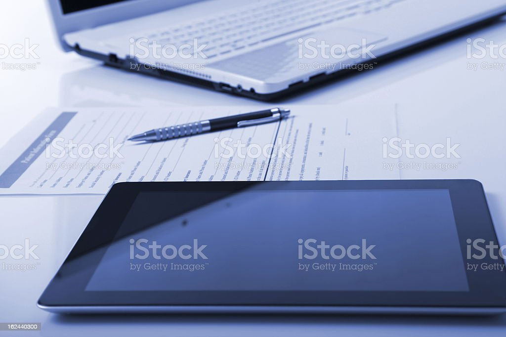 Tablet and laptop with medical paper in the middle stock photo
