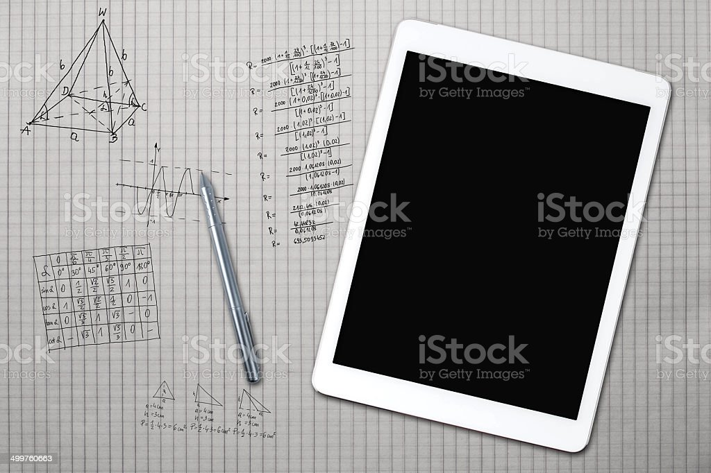 Tablet and mathematical sketches on a sheet of squared royalty-free stock photo