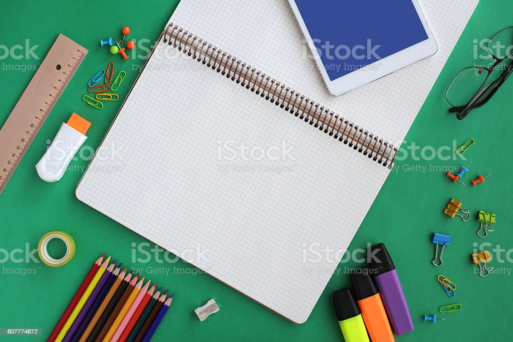 Tablet and notebook on green backgraund stock photo