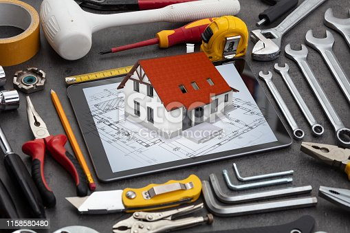 istock Tablet and tools with 3d home plan concept 1158580480
