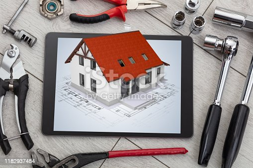 istock Tablet and tools with 3d home plan concept 1182937484