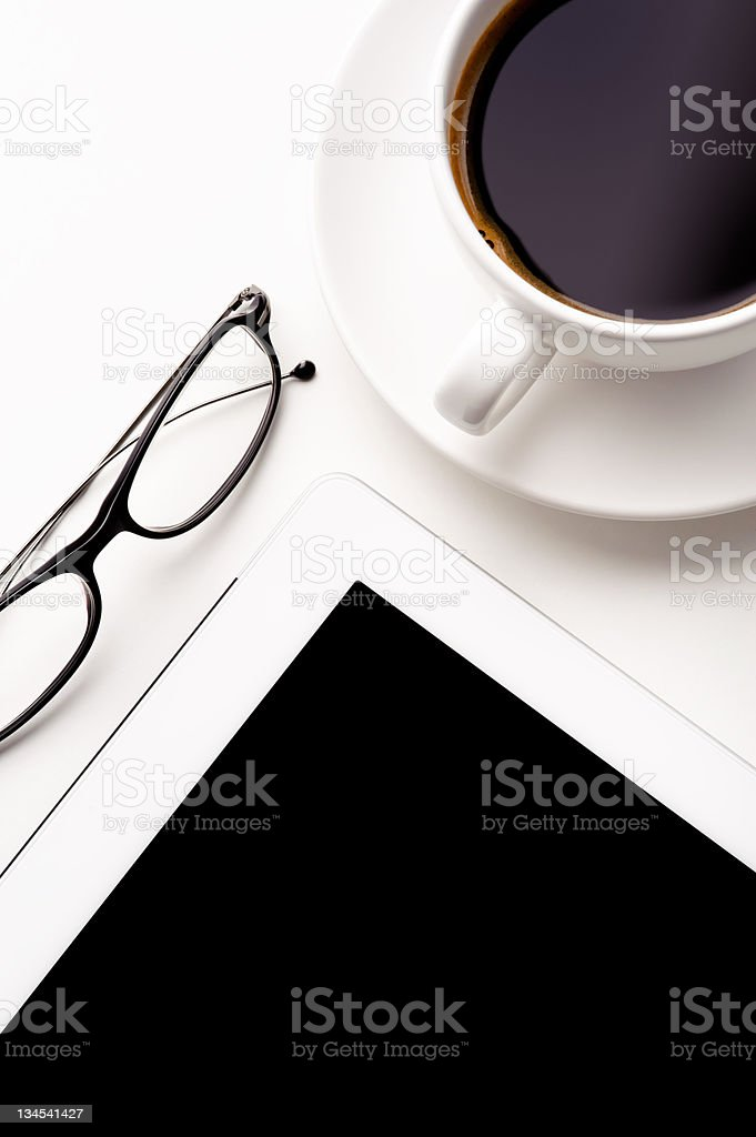 Tablet, coffee cup and glasses on a white table royalty-free stock photo