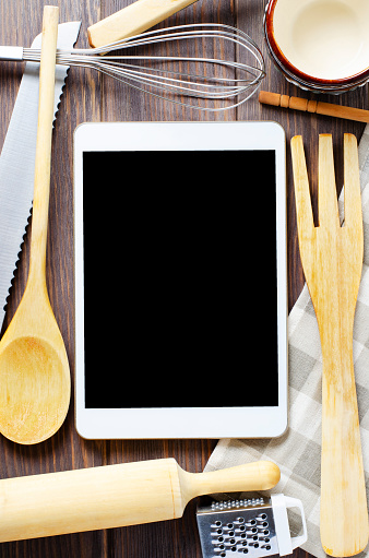 A tablet computer and cooking battery on a brown wooden background. Copy space. Concept of cooking recipes.