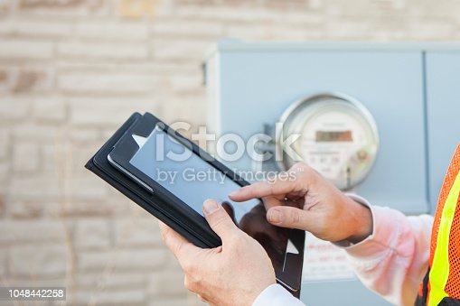 Close up of a technician using a tablet computer to record information from an electricity meter.