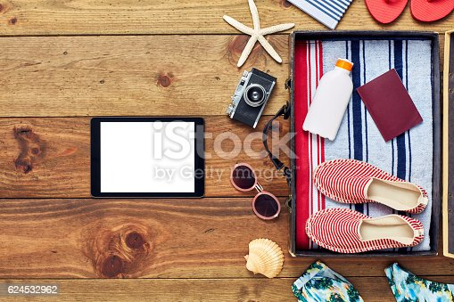 941183588 istock photo Tablet computer by open suitcase with summer vacation equipment 624532962