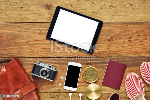 941183588 istock photo Tablet computer by travel accessories flat lay on wooden floor 624528128