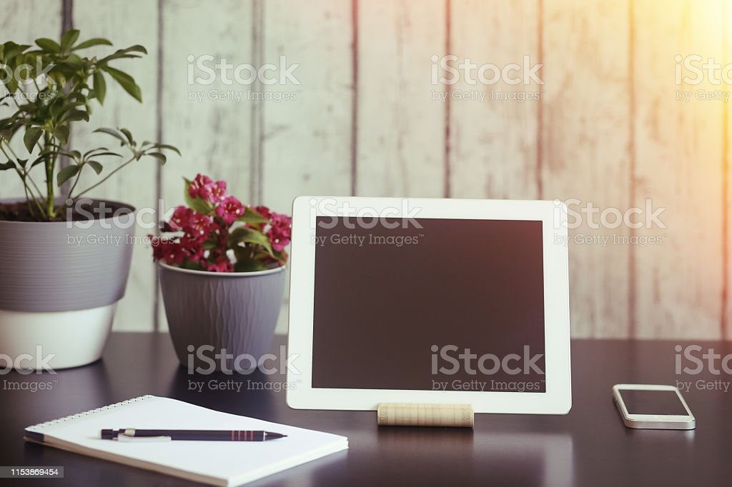 Tablet computer, home plant, notebook, phone on the table. Work at...
