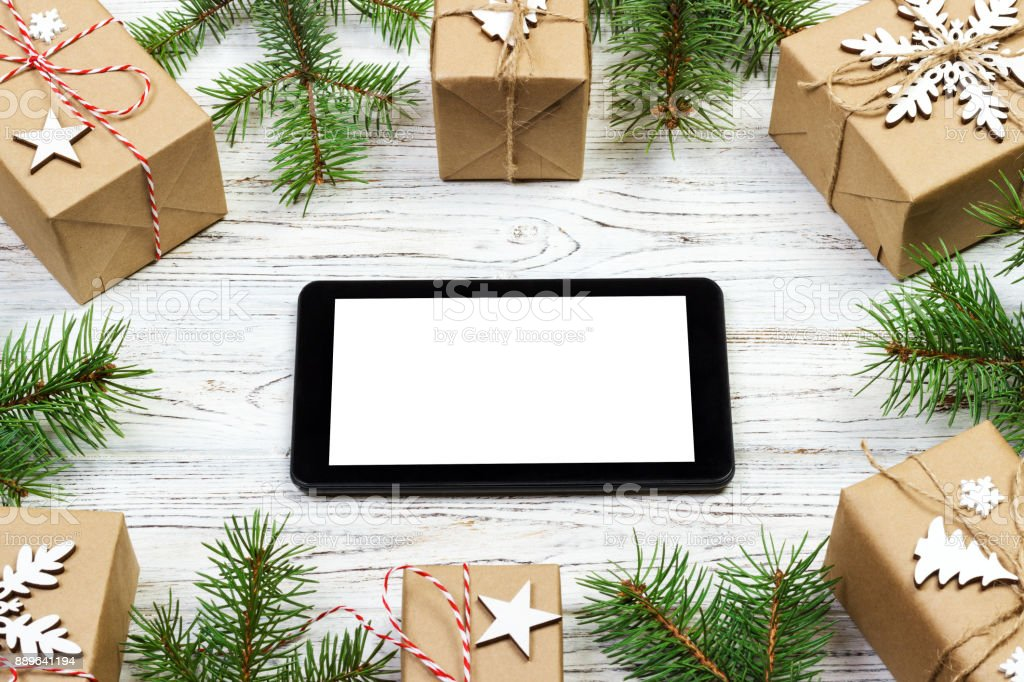 Tablet computer or notebook in christmas frame with gift box. fir...
