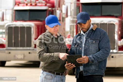 A royalty free image from the trucking industry of two truck drivers having a meeting using a tablet computer.