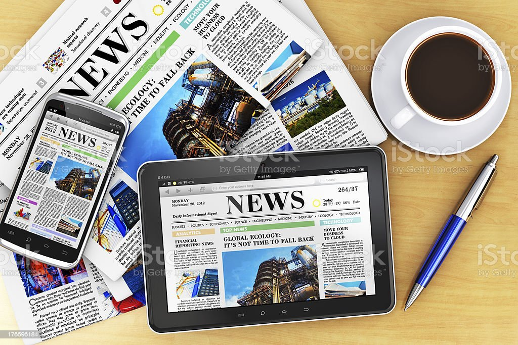 Tablet computer, smartphone and newspaper on table stock photo
