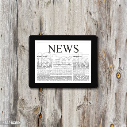 932821906 istock photo Tablet computer with business news 455240359