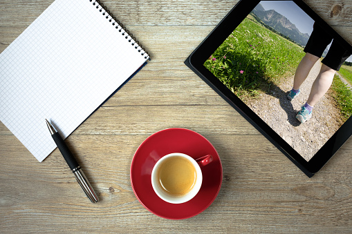 Tablet computer with hiking woman and note pad and coffee cup