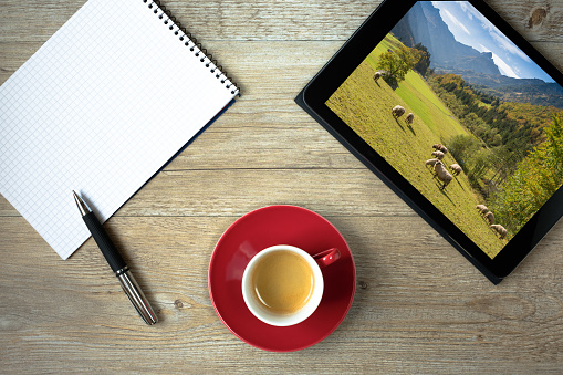 Tablet computer with picture of mountains in Allgäu and note pad